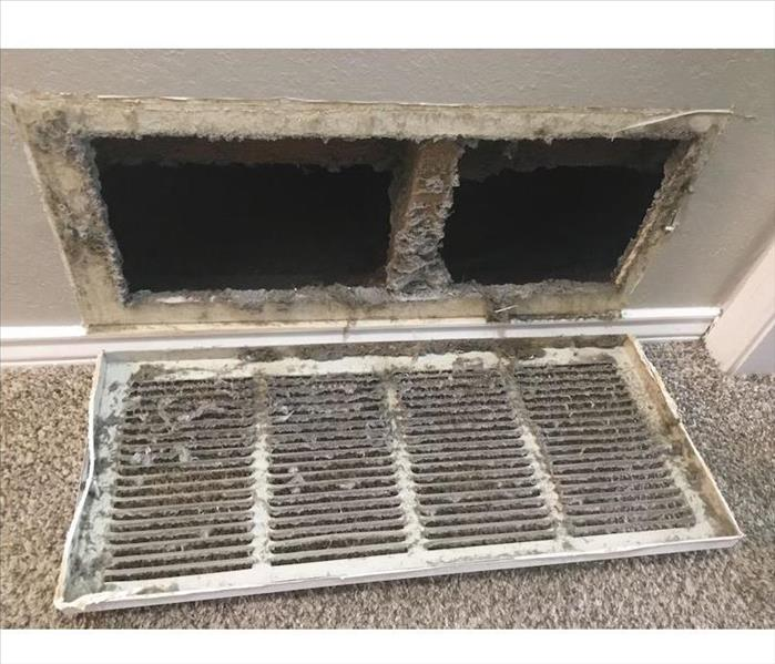 Ductwork with vent removed and debris on grate
