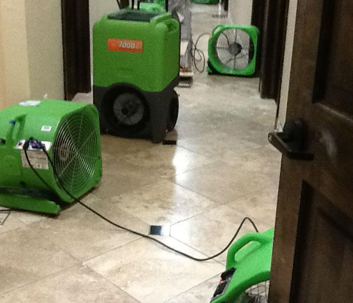 Green dehumidifier and 3 air movers sitting in a hallway with a light brown tile floor and dark brown door in the foreground.