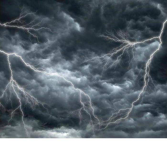 lightning bolts across dark stormy sky with gray and white rumbling clouds in the background